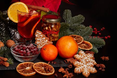 Still life with glasses of mulled wine or fruit tea, Red Poinsettia flowers, fir branch and spices on a dark background. New year and Christmas table setting. Greeting card. Banco de Imagens