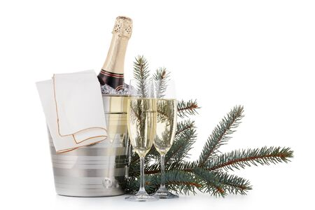 Still life with cooled champagne bottle  standing  in a bucket with ice, two full champagne flutes and fir tree branch  isolated on a white background with copy space, Christmas and New Year celebration