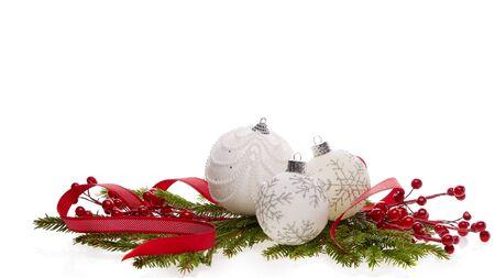 Natura morta con palline bianche scintillanti, nastro rosso e rami di abete isolati su sfondo bianco. Capodanno e addobbi natalizi