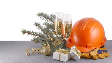 Construction protective clothes (hard hat, gloves and earphones),  fir tree branches, Christmas decorations and two glasses with champagne standing on glittering silver surface. Copy space. New Year and Christmas