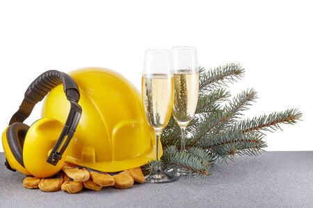Construction protective clothes (hard hat, gloves and earphones),  fir tree branches and two glasses with champagne standing on glittering silver surface. Copy space. New Year and Christmas