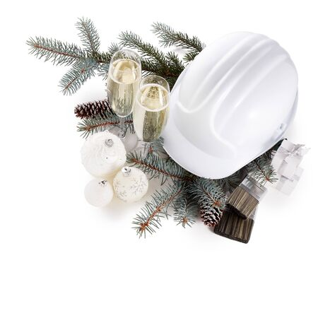 Construction hard hat, fir branches, two glasses with champagne, gift boxes, Christmas ornament isolated on white background. New Year and Christmas construction background, Top view with copy space Stok Fotoğraf