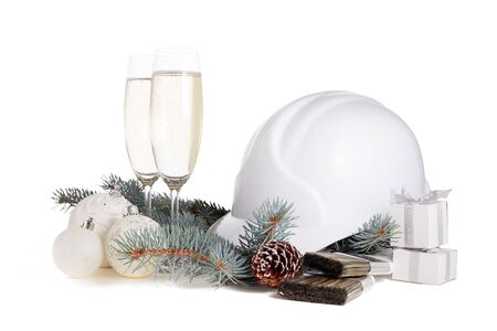Construction hard hat, fir tree branches, two glasses with champagne, gift boxes and Christmas ornament isolated on a white background. New Year and Christmas construction background Stok Fotoğraf