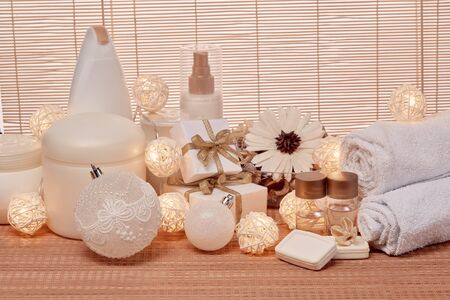 Spa still life with cosmetic creams,  towel, gift boxes and Christmas ornaments standing on bamboo mat. New Year and Christmas Healthy lifestyle, body care, Spa treatment and relaxation concept