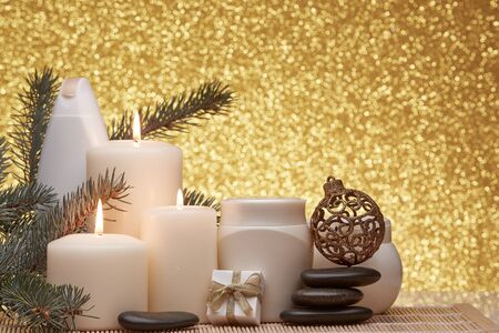 Spa still life with cosmetic creams, candles, fir branches, black stones, gift box and Christmas ornaments on a gold background. New Year and Christmas vacation Healthy lifestyle, body care, Spa treatment and relaxation concept.