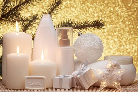 Spa still life with cosmetic creams, candles, fir branches, gift boxes and Christmas ornaments on a gold background. New Year and Christmas vacation