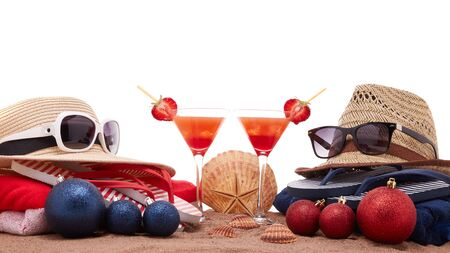 Beach accessories (flip flops, straw hats, seashells, sand, sunglasses), two glasses of cocktail, christmas ornaments on white background. Christmas. Winter  vacation  in warm countries, beach holiday
