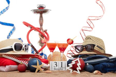 Beach accessories, seashells, sand, two glasses of cocktail,  hookah (shisha) and christmas ornaments on white background. New Year. Winter  vacation  in warm countries, beach holiday