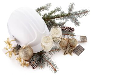 Construction hard hat, fir branches, two glasses with champagne, gift boxes, Christmas ornament isolated on white background. New Year and Christmas construction background, Top view Фото со стока