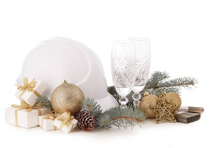 Construction hard hat, fir tree branches, two empty glasses for champagne, gift boxes and Christmas ornament isolated on a white background. New Year and Christmas construction background