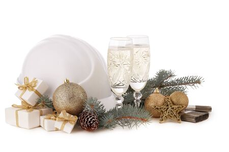 Construction hard hat, fir tree branches, two glasses with champagne, gift boxes and Christmas ornament isolated on a white background. New Year and Christmas construction background Фото со стока - 131495702