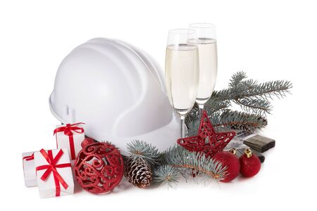 Construction hard hat, fir tree branches, two glasses with champagne, gift boxes and Christmas ornament isolated on a white background. New Year and Christmas construction background Stock Photo