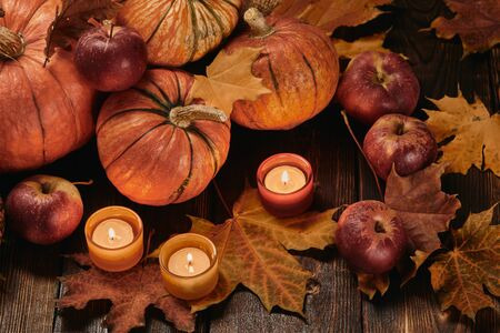 Festive autumn still life  with pumpkins, red apples, candles and leaves on dark  wooden background. Top view. Concept of autumn harvest, happy Thanksgiving  day or Halloween.
