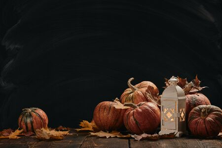 Festive autumn still life  with pumpkins, candle lantern  and leaves on wooden table on black background with copy space. Concept of autumn harvest, happy Thanksgiving  day or Halloween.