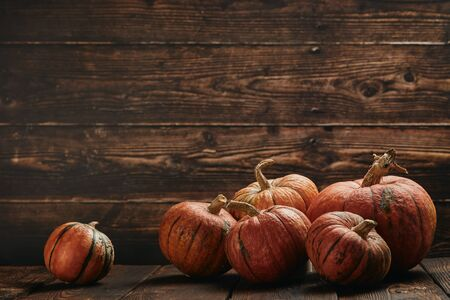 Festive autumn still life  with pumpkins and leaves on wooden  background with copy space. Concept of autumn harvest, happy Thanksgiving  day or Halloween.