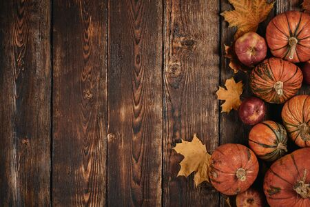 Festive autumn still life  with pumpkins, red apples and leaves on dark  wooden background. Top view with copy space. Concept of autumn harvest, happy Thanksgiving  day or Halloween.
