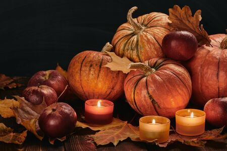 Festive autumn still life  with pumpkins, red apples, candles and leaves on wooden table on black background. Concept of autumn harvest, happy Thanksgiving  day or Halloween.