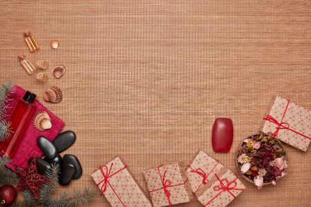 Spa still life with  toiletry, creams, gift boxes and Christmas ornaments on bamboo mat background. Top view with copy space. New Year and Christmas Healthy lifestyle, body care, Spa treatment