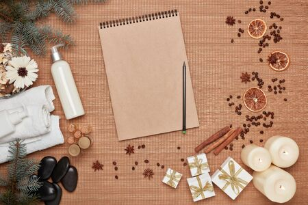Spa still life, blank sheet in notebook, gift boxes, candles  and fir branch on bamboo mat background. Top view. Healthy lifestyle, body care, Spa treatment. New Year and Christmas