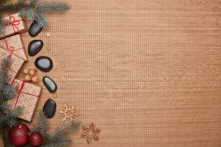 Spa still life with massage stones, oils, gift boxes and Christmas ornaments on bamboo mat background. Top view with copy space. New Year and Christmas Healthy lifestyle, body care, Spa treatment