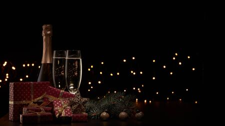 Still life with champagne bottle, two champagne flutes, gift boxes, fir branch, Christmas ornaments and LED lights garland on black background with copy space. Christmas and New Year.  Greeting card