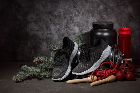 Sports nutrition (supplements), dumbbell, sneakers, jump rope and Christmas ornaments on dark grey background with copy space. Fitness, sport or healthy lifestyle concept. New Year and Christmas.