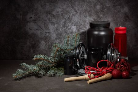 Sports nutrition (supplements), dumbbell, bottle for water, jump rope and Christmas ornaments on dark grey background with copy space. Fitness, sport or healthy lifestyle concept. New Year. Christmas.