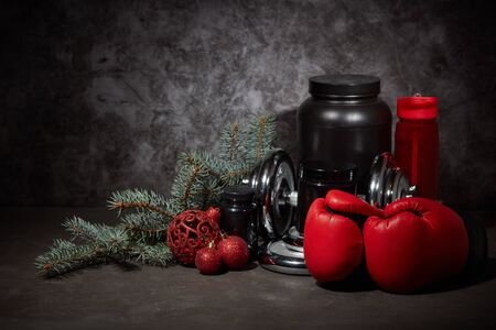Sports nutrition (supplements), dumbbell, boxing gloves, bottle water and Christmas ornaments on dark grey background with copy space. Fitness, sport or healthy lifestyle concept. New Year. Christmas.