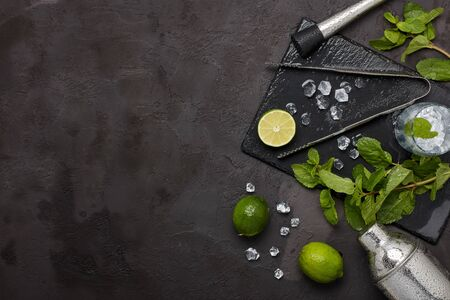 Set of bar tools: cocktail shaker, muddler, ice tongs and glass with ice, lime and mint  on dark stone  table. Top view with copy space. Bartender's tool. Mojito cocktail making. Banco de Imagens