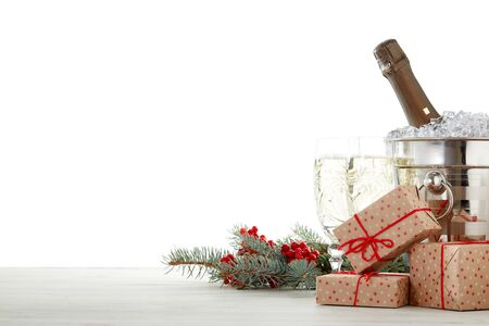 Still life with champagne bottle standing in bucket with ice, champagne flutes, gift boxes and fir branch on wooden table on white background with copy space. Christmas and New Year.  Greeting card