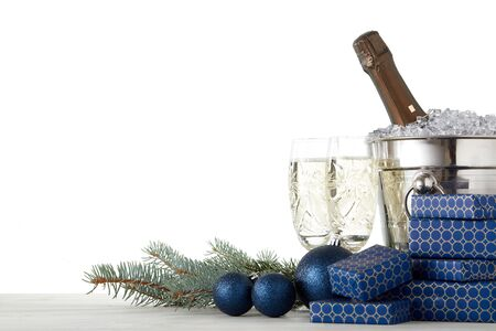 Still life with champagne bottle standing in bucket with ice, champagne flutes, gift boxes, fir branch, Christmas decoration on wooden table on white background with copy space. Christmas and New Year