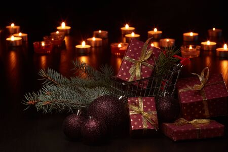 Shopping trolley, gift boxes and Christmas decoration with burning candles on a black background, Christmas and New Year shopping. Winter sale.