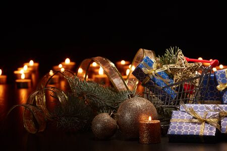Shopping trolley, gift boxes and Christmas decoration with burning candles and fir tree branch on  black background with copy space, Christmas and New Year shopping. Winter sale.