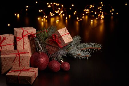 Shopping trolley, gift boxes and Christmas decoration with LED lights garland on a black background with copy space, Christmas and New Year shopping. Winter sale.