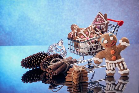 Shopping trolley with gingerbread cookies and christmas decorations standing on a blue background with reflection. Christmas and New Year sale.