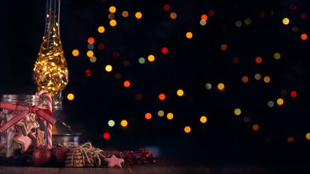 Christmas decor and gingerbread cookies lying on a wooden table on a dark background with light of garland. Copy space for text. Christmas and New Year.