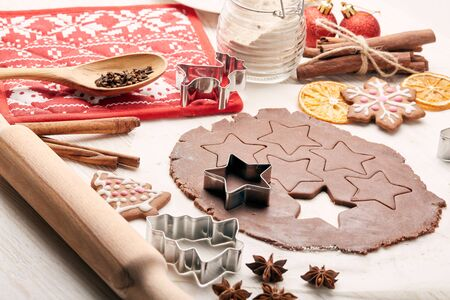 Decorating gingerbreads. Dough, rolling pin, shape cutter for handmade cookies, confection lying on the wooden background. Christmas and New Year treats.