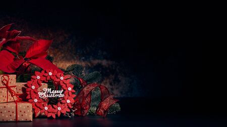 Christmas decoration with Red Poinsettia flowers (Euphorbia Pulcherrima), fir branch and gift boxes on a dark background.  Christmas background with copy space. Greeting card.