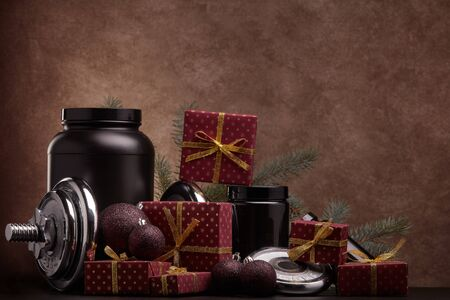 Sports nutrition (supplements), sports equipment, fir branch and  gift boxes on dark brown background with copy space. Fitness, sport, healthy lifestyle concept. New Year. Christmas.