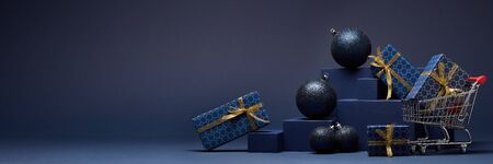Shopping trolley, gift boxes and Christmas ornaments on dark blue background with copy space.  Christmas and New Year shopping. Winter sale. For design of advertising, greeting card Stock Photo