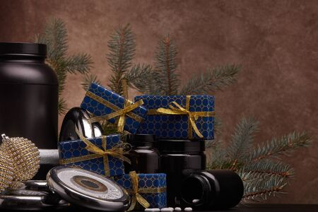 Sports nutrition (supplements), sports equipment, fir branch,  gift boxes, Christmas ornaments on dark brown background with copy space. Fitness, sport, healthy lifestyle concept. New Year. Christmas. Stock Photo