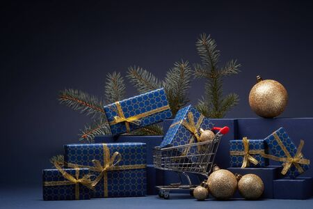 Shopping trolley, gift boxes, fir branch and Christmas ornaments on dark blue background with copy space.  Christmas and New Year shopping. Winter sale. For design of advertising, greeting card