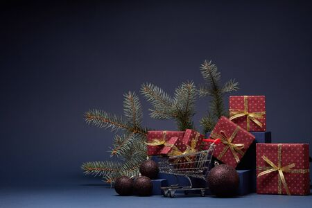 Shopping trolley, red gift boxes, fir branch and Christmas ornaments on dark blue background with copy space.  Christmas and New Year shopping. Winter sale. For design of advertising, greeting card Stock Photo