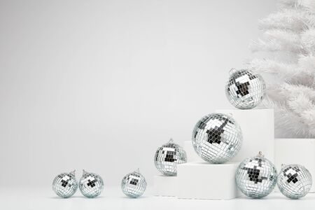 Festive composition with white geometrical figures, Christmas fir tree and mirorr balls isolated on white background with copy space. For design of advertising,  web design. Christmas and New Year