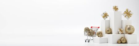 Shopping trolley, gift boxes and Christmas decorations isolated on white  background with copy space. Christmas and New Year shopping. Winter sale. For design of advertising, web design Stock Photo