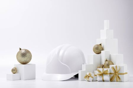 Construction hard hat, white fir tree,  gift boxes and Christmas ornament on a white background with copy space. New Year and Christmas construction background