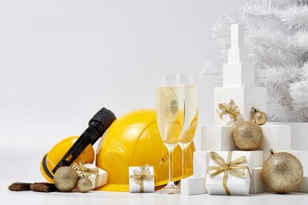 Construction protective earphones and hard hat, fir tree, flutes with champagne, gift boxes and Christmas ornament on a white background. New Year and Christmas construction