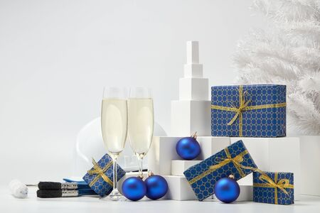 Construction hard hat, white fir tree, two glasses with champagne, gift boxes and Christmas ornaments on a white background. New Year and Christmas construction background Stock Photo