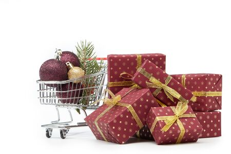 Shopping trolley, gift boxes and Christmas decoration isolated on white  background, Christmas and New Year shopping. Winter sale. Stock Photo
