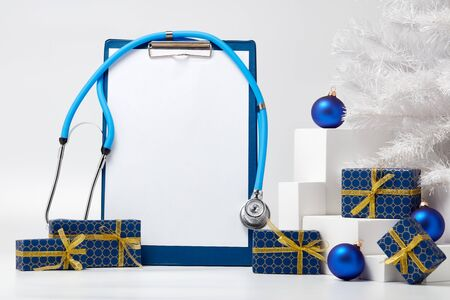 Stethoscope, blank clipboard, white fir tree, gift boxes and Christmas decorations on white background with copy space. Medical concept. Greeting card. New Year and Christmas. Stock Photo